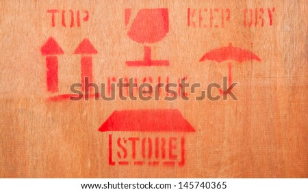 Fine image close-up of grunge red fragile symbol on wood board - stock photo