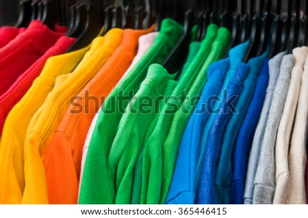 Fine knit pullovers in rainbow colors arranged on hangers; Inexpensive mass-produced goods; Color variety - stock photo