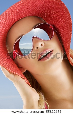 fine portrait of young cute woman with red summer hat and sun glasses looking at the sea in a sunny day - stock photo
