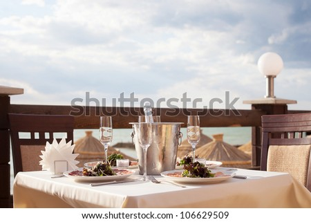 Fine restaurant dinner table place setting: wineglass, shampagne - stock photo