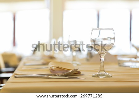 Fine restaurant table - place setting, napkin & wineglass - stock photo
