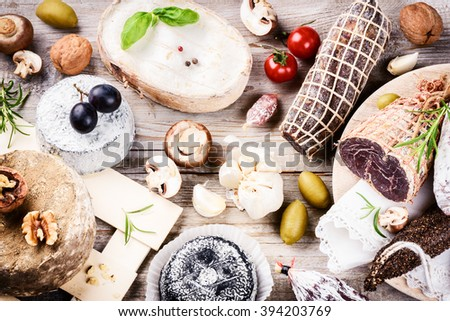 Fine selection of dry meat, sausages and French cheese. Gourmet dinner concept - stock photo