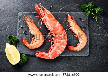 Fine selection of jumbo shrimps for dinner on stone plate. Food background - stock photo