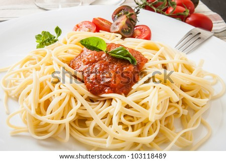 fine spaghetti with tomato bacon and cheese with basil leaves