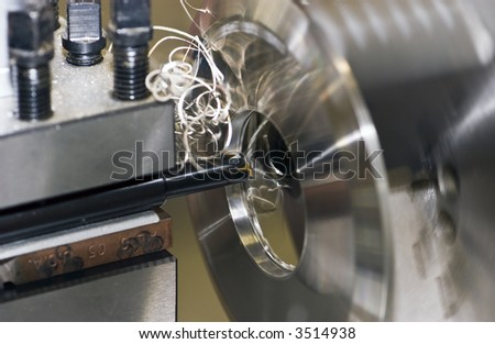 Fine turnings fly off a fast spinning metal lathe - stock photo