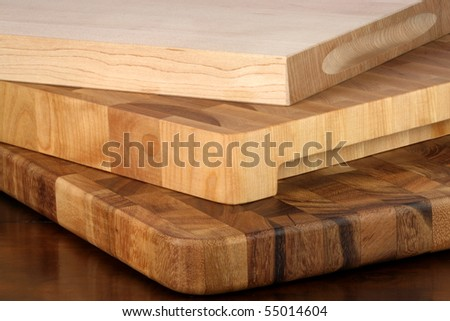 fine wood cutting boards one on top of each other over rustic wood table - stock photo