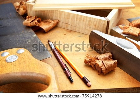 Fine wood working. Saw, hand plane, pencils and a wooden shavings on a work desk under incandescent light. - stock photo