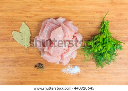 finely chopped juicy pink pieces of meat on a kitchen wooden board, prepared for the production of beef stew with spicy condiments - pepper, salt, parsley, bay leaf ... - stock photo