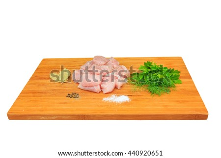 finely chopped juicy pink pieces of meat on a kitchen wooden board, prepared for the production of beef stew with spicy condiments - pepper, salt, parsley, bay leaf ...  isolated background - stock photo