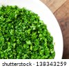 Finely chopped parsley in a white dish on a old kitchen table. - stock photo