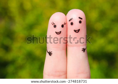 Finger art of a Happy couple. A man and a woman hug on the background of green leaves - stock photo