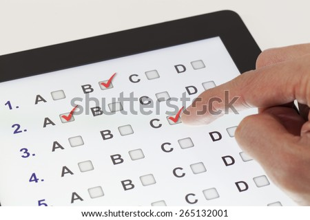 Finger clicking on a tablet with multiple-choice questions - stock photo