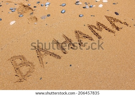 Finger drawing on a sandy beach - Bahama word.