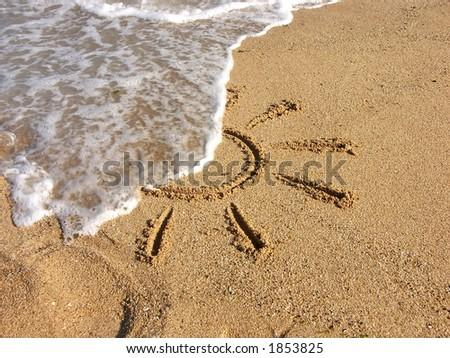 Finger drawn sun on sand being washed by sea wave - stock photo