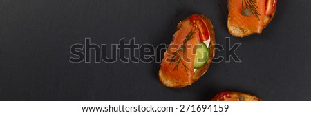 Finger food canape with smoked salmon. Panoramic image. Selective focus. - stock photo