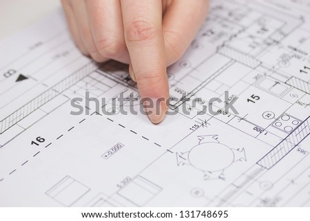 Finger from an unknown person is showing in the plan of the house. - stock photo