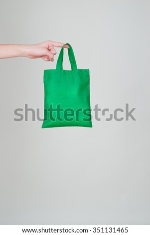 Finger holding a green textile bag -  ecological shopping concept