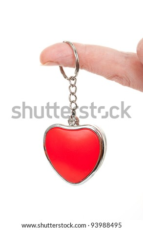 Finger holding a red heart on a chain