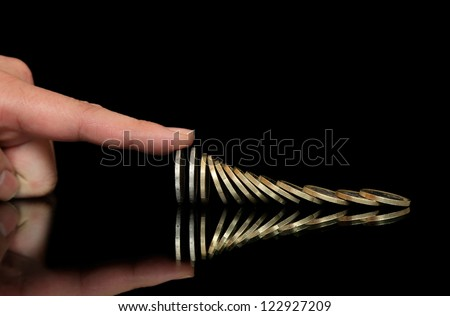 finger is stopping the fall of coins - stock photo
