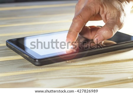 Finger man or businessman points on a touch screen tablet computer. Luminous screen. Concept: bright idea. a businessman using the touchscreen of a tablet with his hands - stock photo