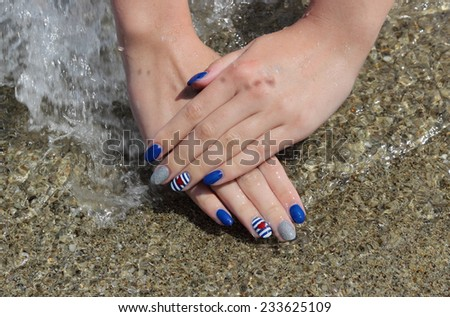 Finger nail treatment ,hands with painted fingernails at sand in water - stock photo