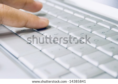 Finger of child on computer keyboard - stock photo