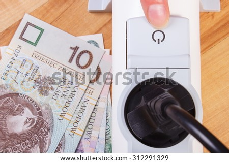 Finger of woman turns off electrical power strip with connected plug, polish currency money, concept of saving money on electricity, energy costs - stock photo