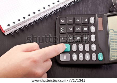 finger on calculator, pressing add button, close up - stock photo