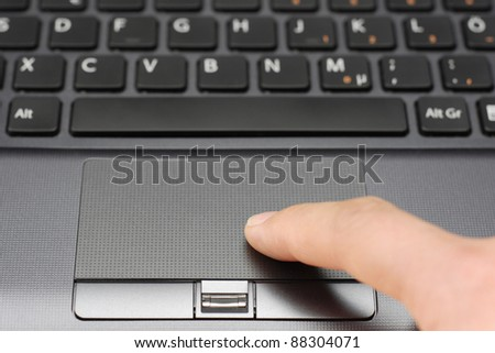 Finger on Notebook Touchpad - stock photo