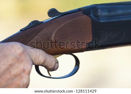 Finger on the trigger of a shotgun - stock photo