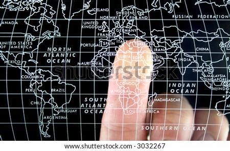 Finger on world Map - stock photo