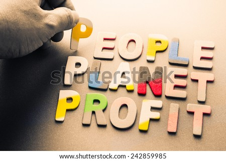 Finger pick a wood letters of People, planet, profit word - stock photo