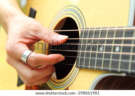 Finger picking the guitar - stock photo