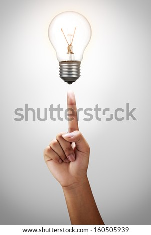 Finger point to light bulb - stock photo