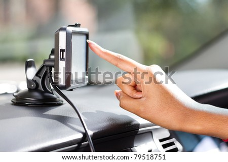finger pointing at car GPS navigation system - stock photo