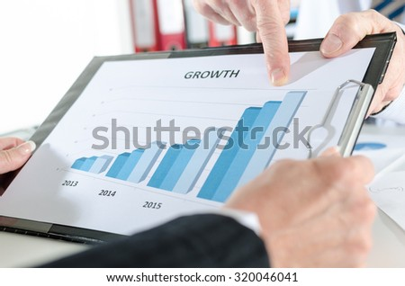 Finger pointing on a graph showing growth - stock photo