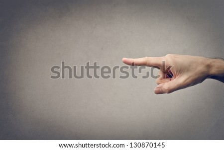 finger pointing on a gray background - stock photo