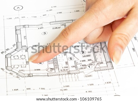 finger pointing on blueprints - stock photo