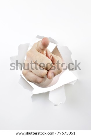 Finger pointing through hole torn in white paper - stock photo