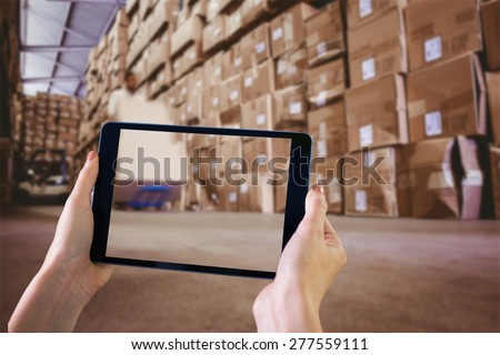 Finger pointing to tablet against worker with fork pallet truck stacker in warehouse - stock photo