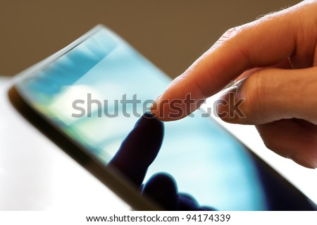 Finger pointing to the screen of a tablet-pc - stock photo