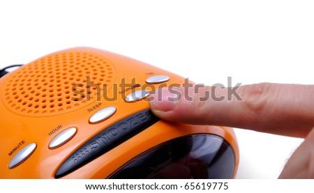 Finger pressing a snooze alarm button - stock photo