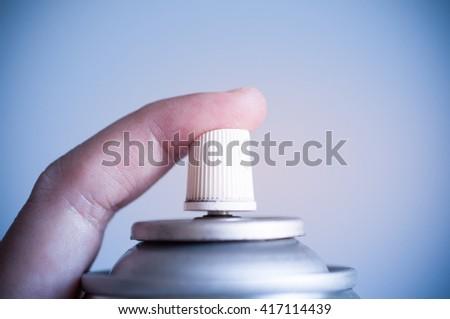 Finger pressing aerosal spray can. - stock photo