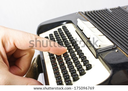 Finger pressing black accordion buttons