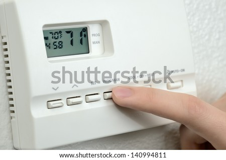 finger pressing button  on digital thermostat - stock photo