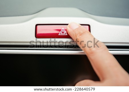 Finger pressing car emergency button - stock photo