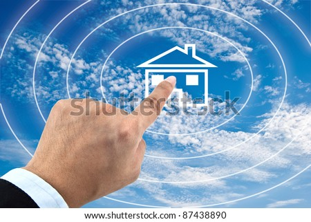 Finger pressing home icon on the sky - stock photo