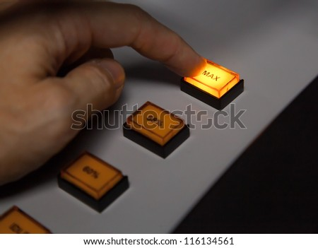 Finger pressing max button on industrial power control panel. Selective focus - stock photo