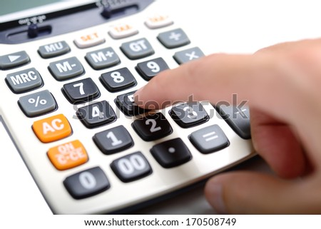 Finger pressing on calculator at number 5 - stock photo