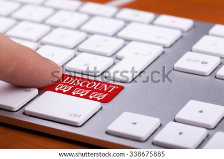 Finger pressing on discount button on red keyboard. Online sales. Three shopping carts are next to the finger and words - stock photo